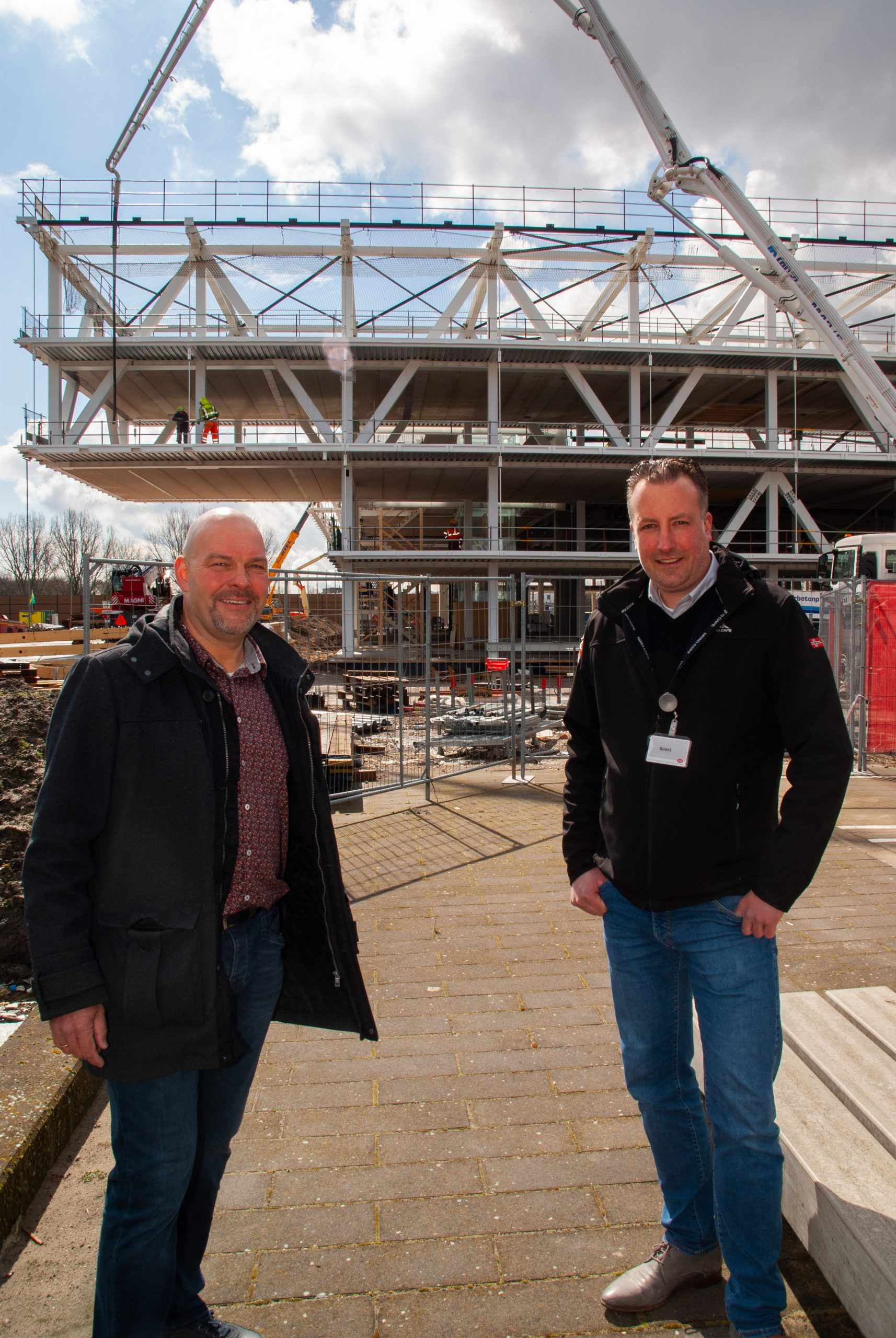 Edwin Hazelzet van Lely en Conor Brouwer van IDDS met op de achtergrond de nieuwbouw in volle gang